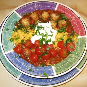 Won a chili cookoff with this particular version using cubed steak and smoked hocks covered with tater tots cherry tomatoes cheddar and sour cream.