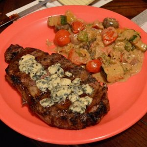 Grilled steak with blue cheese sauce and a vegetable medley in garlic butter cream sauce.